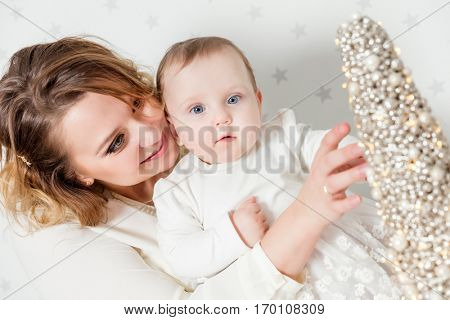 Mother plays with her baby daughter. Portrait on starry wallpaper background. Maternity love