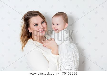 Mother with her newborn baby daughter. Portrait on starry wallpaper background. Maternity love