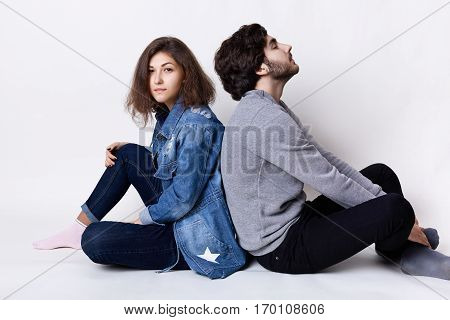 Thoughtful couple sitting on the floor back having rest. A young female dressed in jean clothes and stylish guy dressed casual clothes relaxing on the floor and dreaming about something