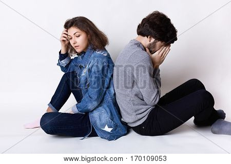 Feelings and attitudes. A couple sitting on the floor backs having tired and sad expression after a little quarrel. Couple having argument sitting back to back taking offence