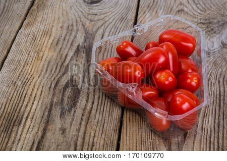 Small red oblong tomatoes on wood. Studio Photo