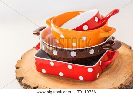 colorful ceramic polka dots dishes on wooden backgound