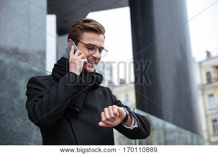 Smiling business man with phone on the street. man looking at wristwatch