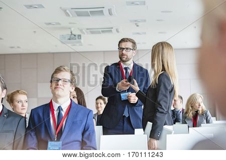 Business people holding microphone while standing during seminar