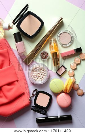 Macaroon cookies and makeup products on color background