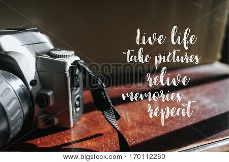 Isolated calligraphy on Camera film on brown wooden stairs. Quote about photo and photography. Live life take pictures relive memories repeat.