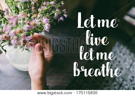 Life quote. Motivation quote on soft background. The hand touching purple flowers. Let me live, let me breathe.