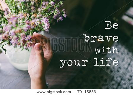 Life quote. Motivation quote on soft background. The hand touching purple flowers. Be brave with your life.