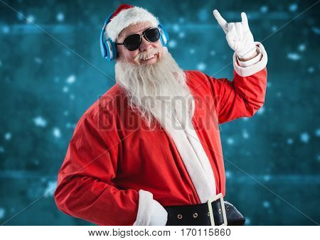 Santa gesturing while listening music on headphones against digitally generated background