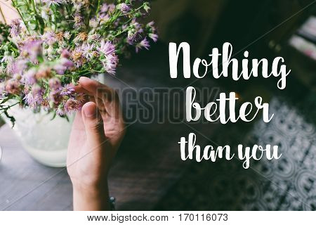 Life quote. Motivation quote on soft background. The hand touching purple flowers. Nothing better than you.