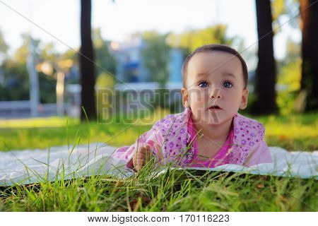 Cute baby girl on the grass in the park