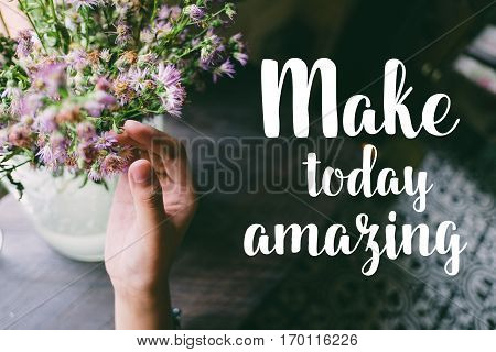 Life quote. Motivation quote on soft background. The hand touching purple flowers. Make today amazing.