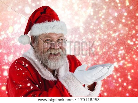 Portrait of santa pretending to hold digital generated christmas gifts against digitally generated background