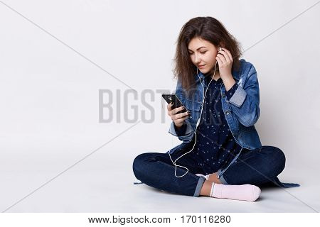 People technology and communication. A pretty young dark-haired girl listening to the music with her cell-phone holding her hand on her earphones sitting crossed legs in white studio