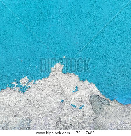 Fragment of wall with broken stucco. Old azure wall with damaged shabby color plaster. Distressed wall background. Concept of renewal of restore and repair.