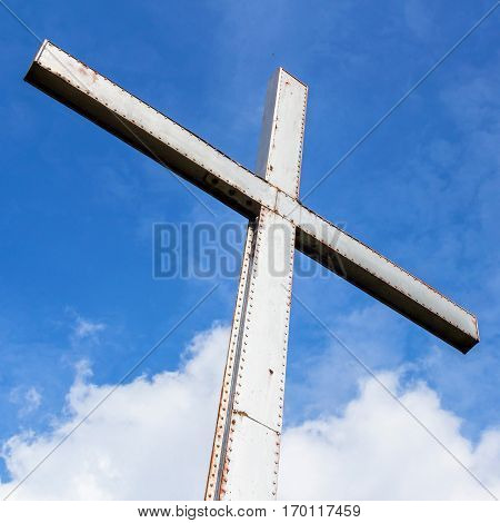 Iron cross over a blue sky with clouds background. Universal symbol of God and of faith. Belief or resurrection. Easter.