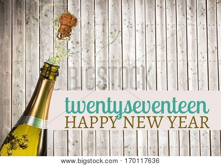 2017 happy new year wishes with opened champagne bottle cork popping against wooden background