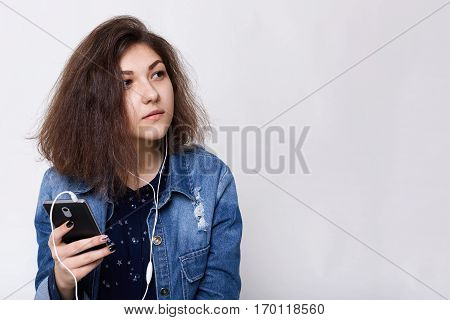 People and technology concept. Fashion lifestyle portrait of hazel-eyed girl wearing jean jacket and dark skirt listening to the music with her earphones and mobile looking aside having dreams