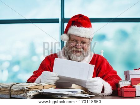 Santa claus reading a letter and smiling