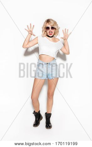 Fashion beauty girl in sunglasses showing cat claw nails. Full length portrait of blond young woman over white background. Crazy and rebel hipster concept isolated