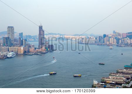 Skyscrapers on sea shore in business area, many ships at morning in Hong Kong, China, view from China Merchants Tower