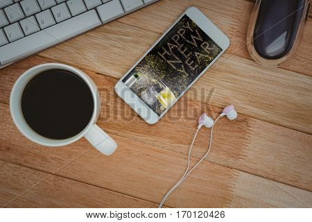 White smartphone with cup of coffee against champagne pouring on flute