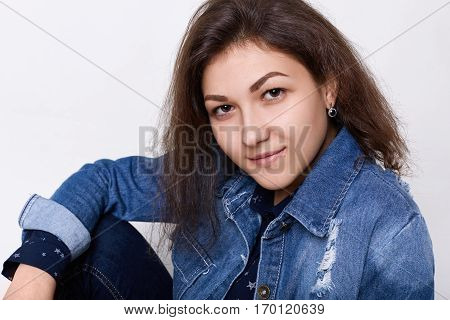 A close-up of beautiful hazel-eyed girl with attractive features dark fluffy hair wearing jean jacket looking attentively into camera isolated over white background. Style youth and fashion concept