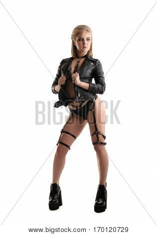 Young sexy blonde in rocker black leather jacket, leather belts on heaps and high heel platform boots in studio