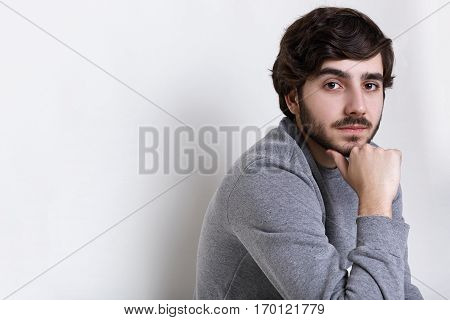 Sideways portrait of young hipster having dark beard with moustache big dark eyes thick eyebrows and fashionable hairstyle holding his hand on his chin having clever serious expression.