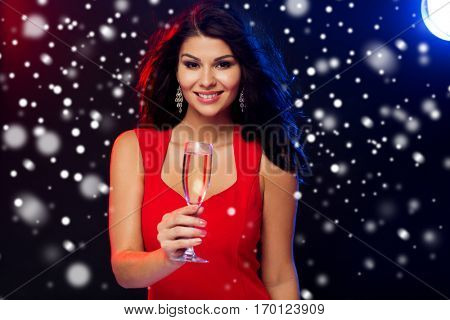 people, winter holidays, party, night lifestyle and leisure concept - beautiful sexy woman in red dress with champagne glass at nightclub over snow