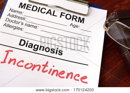 Medical form with diagnosis Incontinence on a table.