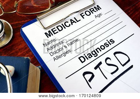 Medical form with diagnosis PTSD on a table.