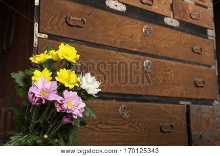 Chrysanthemum flowers in front of japanese antique chest