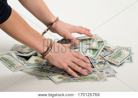 hands handcuffed over a bunch of dollars over white background