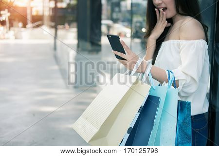 young aisin woman using her smartphone and hold shopping bag while doing some shopping in a street shopping mall vintage tone and outdoor.