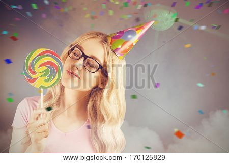 A beautiful hipster holding a giant lollipop against illuminated disco lights at disco