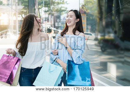 two young happy asian women shopping outdoor shopping mall in a holiday vintage tone.
