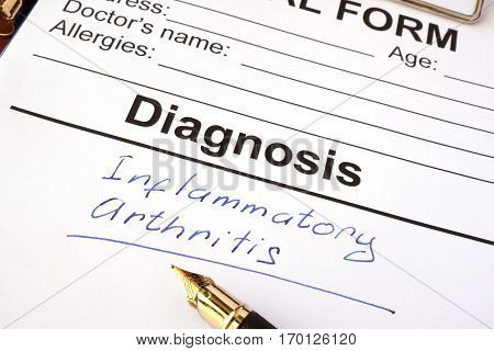 Medical form with diagnosis inflammatory arthritis on a table.