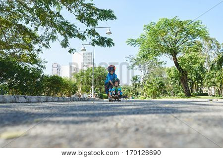 Cute little boy in helmet and knee pads riding skateboard while sitting on it, his elder brother pushing him down the road, surface level shot