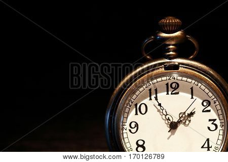 Closeup of old pocket watch on dark background with free space