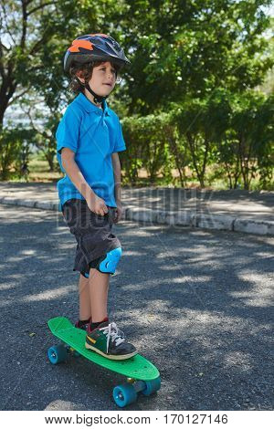 Thoughtful curly little boy standing with one leg on bright green penny board and looking into distance in summer park