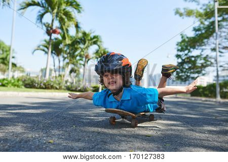 Curly little boy in blue polo T-shirt lying on skateboard on his belly and pretending to fly in sunny park