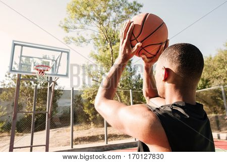 Image of young attractive african basketball player practicing in the street with basketball hoop. Looking at hoop.