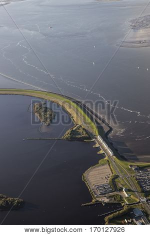 Aerial coastal view of the shore of Ameland Frisian Island with a road on a dike a car park surrounded by sea The Netherlands