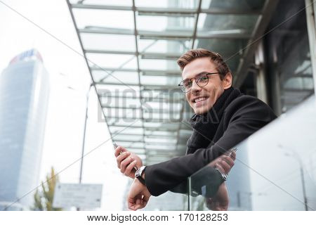 Business man near the office looking at camera. man in glasses with phone