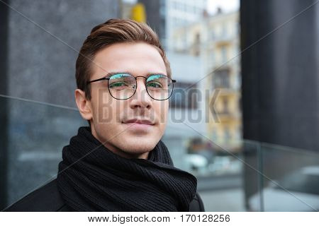 Close up business man in glasses looking at camera on the street