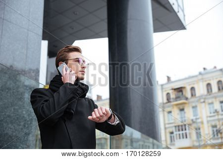 Business man with phone on the street. side view. from below