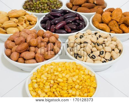 Almond, Cashew nuts, yellow bean, green bean, rice, fettucine, all put on small white cup and on white background