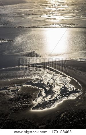 aerial view of estuary mudflat wetland of the shore of Ameland island in the reflecting sunset The Netherlands