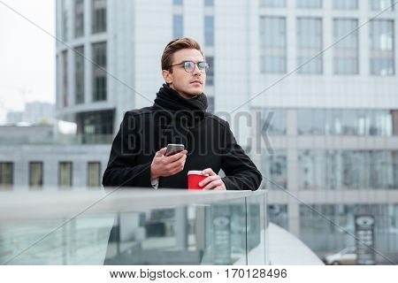 Handsome business man in glasses and warm clothes with coffee and phone outdoors